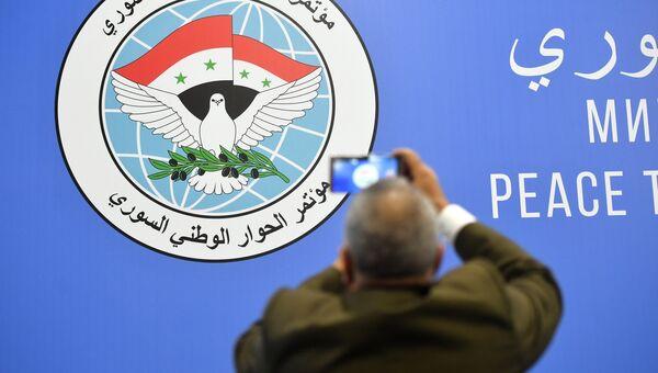 Мужчина фотографирует эмблему конгресса сирийского национального диалога в Сочи