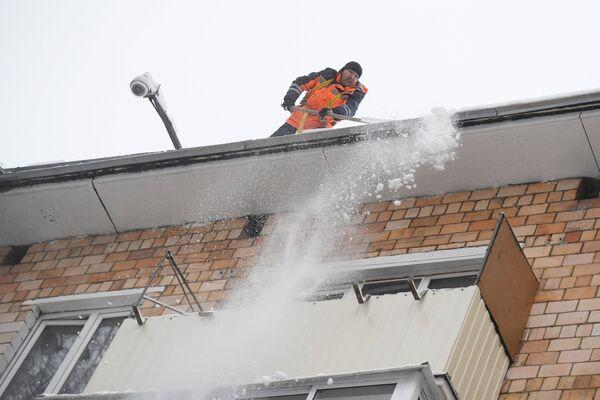 Сотрудник коммунальной службы во время чистки кровли от снега в Москве