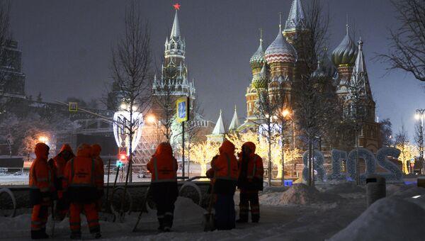 Сотрудники коммунальных служб убирают снег на улице в Москве