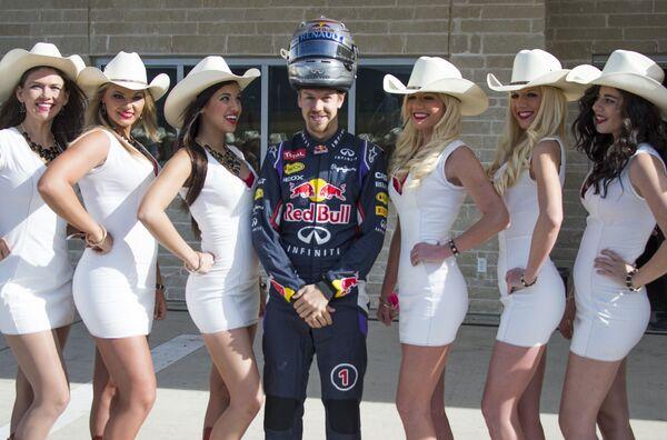 Немецкий автогонщик Себастьян Феттель фотографируется с грид-герлз во время этапа Гранпри Формулы-1 на гоночной трассе Трасса Америк в штате Техас, США, 2 ноября 2014