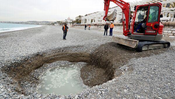 Экскаватор рядом с пятиметровым кратером, который сформировался на пляже Лидо в Ницце, Франция. 1 февраля 201