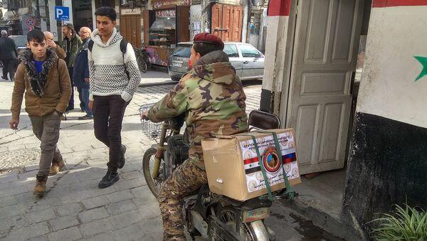 Житель Дамаска с коробкой гумпомощи из России. Архивное фото