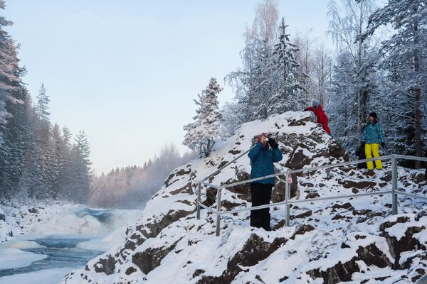 Туристы у водопада Кивач, образуемого падением реки Суны, на территории Государственного заповедника Кивач в Республике Карелия