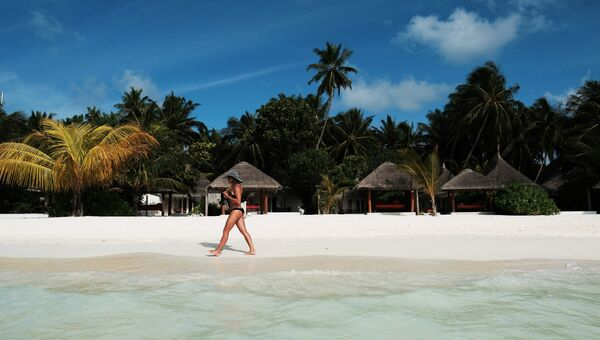 Девушка идет по пляжу одного из Мальдивских островов