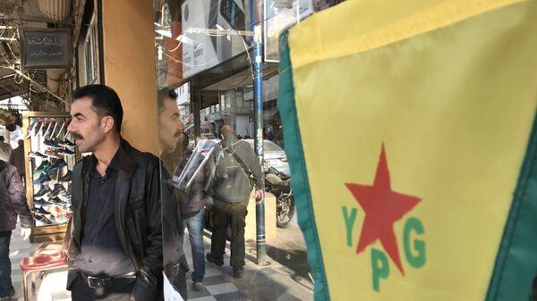 Флаг курдских сил самообороны (YPG) на центральной улице города Африн, Сирия