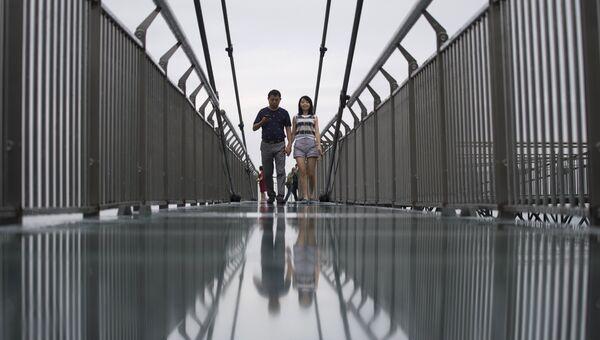 Пара идет по стеклянной дорожке, которая считается самой длиннойм в мире, в парке Ордовик в Ваншэн, Китай. 1 июня 2017