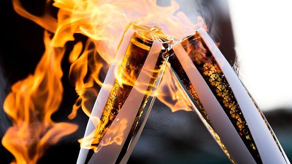 Факелы с Олимпийским огнём во время эстафеты в Пхенчхане