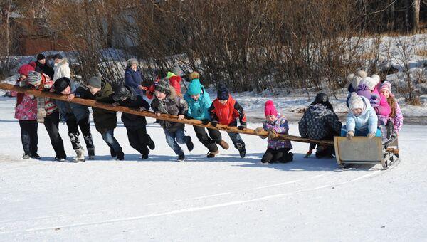 Дети катаются в санях во время праздничных масленичных гуляний в Забайкальском крае