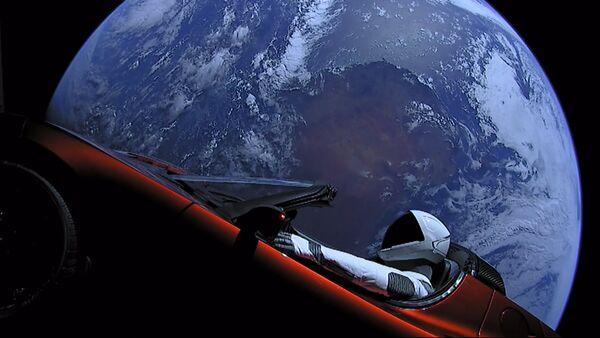 Личный автомобиль главы SpaceX Илона Маска красный кабриолет Tesla Roadster, выведенный на орбиту ракето-носителем Falcon Heavy американской компании SpaceX, с манекеном в скафандре за рулем в космическом пространстве