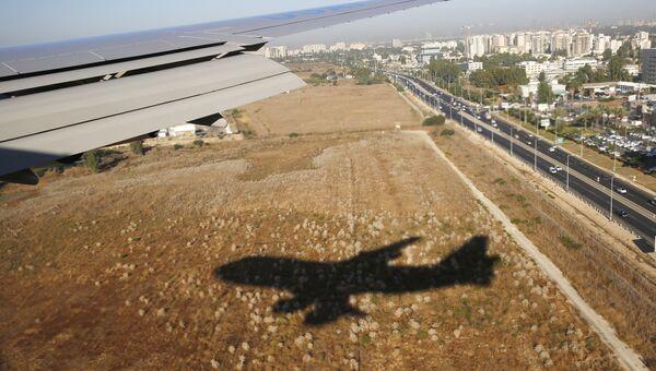 Тень от самолета, прилетающего в международный аэропорт Бен-Гурион в Тель-Авиве, Израиль