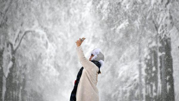 Девушка фотографируется во время снегопада. Архивное фото