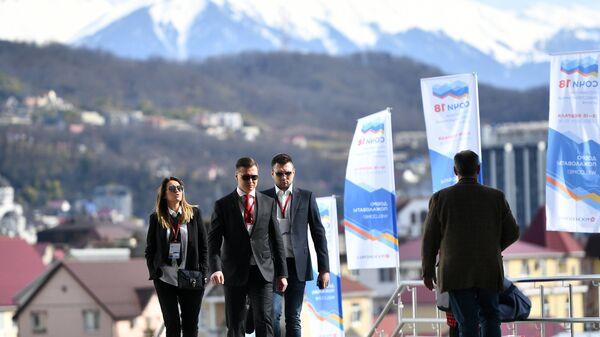 Посетители Российского инвестиционного форума возле здания главного Медиацентра Олимпийского парка в Сочи