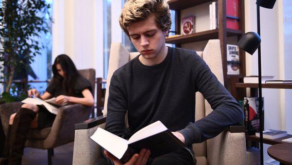 Молодой человек читает книгу. Архивное фото