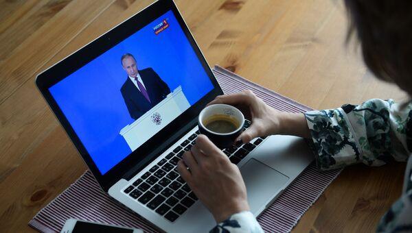 Девушка у себя в квартире в Новосибирске смотрит трансляцию ежегодного послания президента РФ Владимира Путина к Федеральному собранию. 1 марта 2018