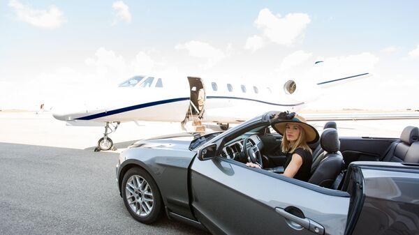 Девушка в автомобиле возле частного самолета