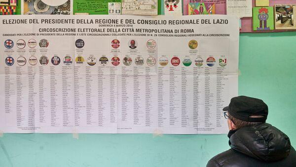Житель Рима на одном из избирательных участков города изучает список партий. Архивное фото