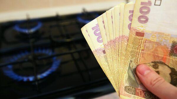 Горящая газовая конфорка и денежные купюры Украины