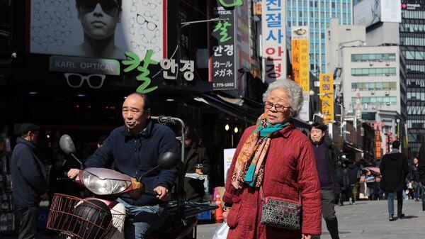 Прохожие в торговом районе Намдемун в Сеуле