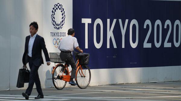Пешеходы проходят мимо символики Олимпийских игр в Токио
