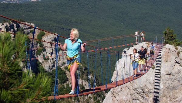 Туристы идут по веревочной лестнице между зубцами горы Ай-Петри в Крыму.