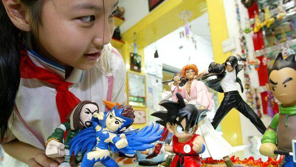 Девочка рассматривает фигурки героев мультфильмов в преддверии Китайского международного фестиваля анимации в Ханчжоу