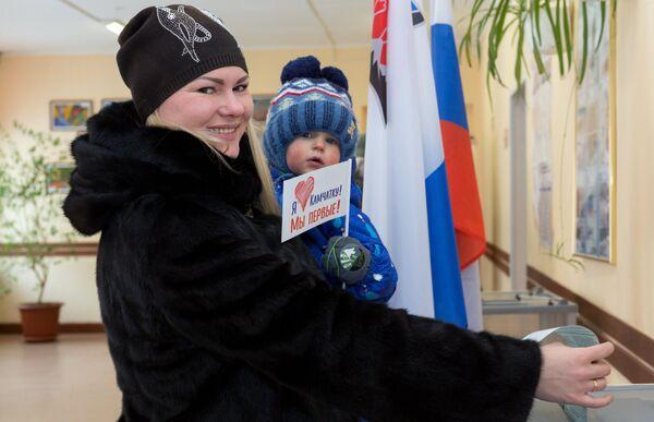 Женщина опускает бюллетень в урну на выборах президента РФ на избирательном участке №51 в Петропавловске-Камчатском.