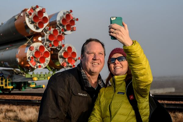 Журналисты фотографируются на фоне ракеты-носителя Союз-ФГ c транспортно-пилотируемым кораблем Союз МС-08 на стартовую площадку космодрома Байконур