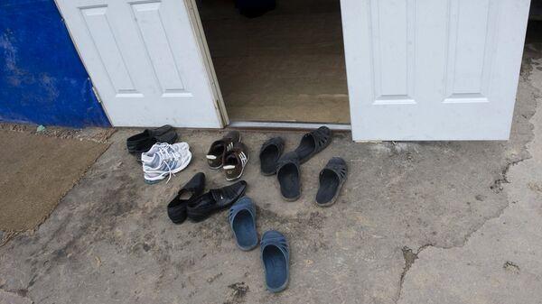 Обувь у двери места жительства мигрантов