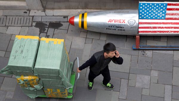 Мужчина с тележкой, груженой коробками с товаром, в Пекине. 23 марта 2018