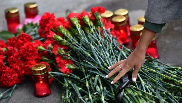 Цветы и свечи в память о погибших в ТЦ Зимняя вишня у здания представительства Кемеровской области в Москве. 26 марта 2018