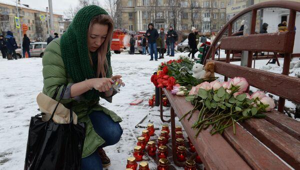 Женщина зажигает свечу возле здания торгового центра «Зимняя вишня» в Кемерово, где произошел пожар