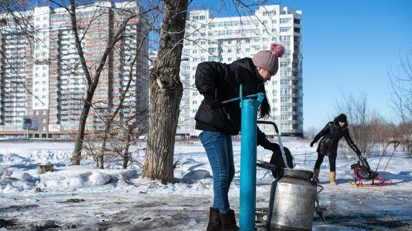 Женщина набирает воду в бидон из колонки