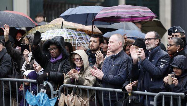 Люди аплодируют во время церемонии прощания с подполковником жандармерии Арно Бельтрамом в Париже