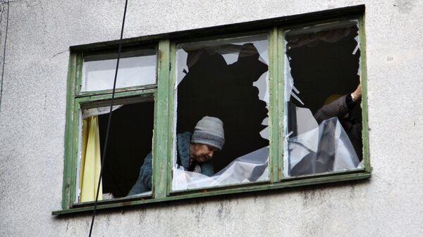 Женщина у окна жилого дома в центре города Ясиноватая, пострадавшего в результате обстрела. Архивное фото
