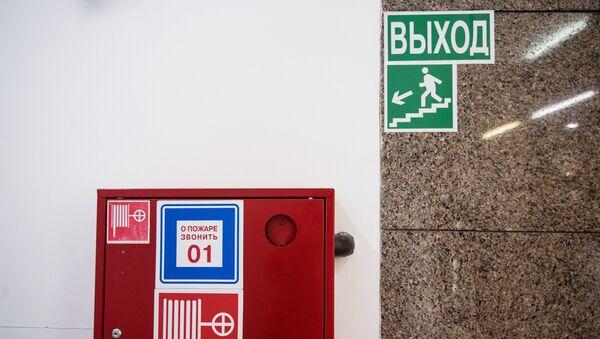 Пожарный шкаф и указатель направления эвакуации при пожаре в торговом центре. Архив