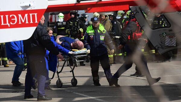 Сотрудники МЧС РФ эвакуируют пострадавшего при пожаре в детском торговом центре Персей в Москве