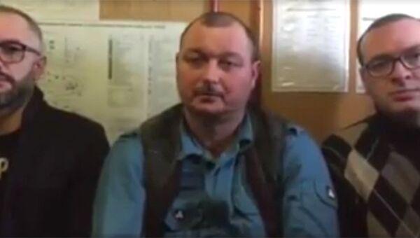 Капитан задержанного в Бердянске судна Норд Владимир Горбенко с адвокатами на стоп-кадре видеозаписи обращения, распространенного в социальных сетях