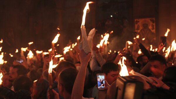 Верующие на церемонии схождения Благодатного огня в храме Гроба Господня. 7 апреля 2018