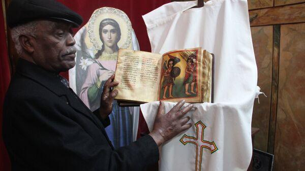 Смотритель эфиопского монастыря Джерси показывает Евангелие XVII века