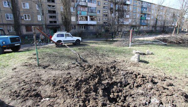 Воронка от снаряда во дворе жилого дома в Донецке. Архивное фото