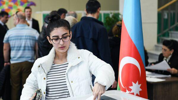 Девушка голосует на выборах президента Азербайджана на избирательном участке в Баку