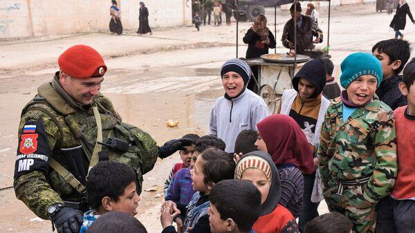 Сотрудник российской военной полиции с сирийскими детьми