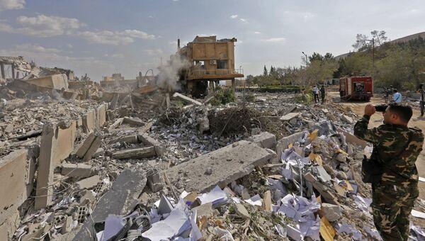 Сирийский солдат на месте разрушенного научно-исследовательского центра в Барзе, Сирия. Архивное фото