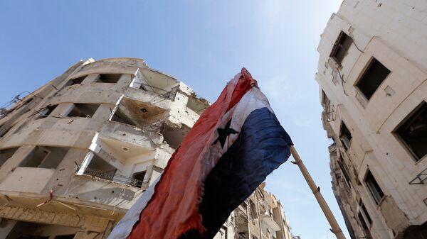 Сирийский флаг на разрушенной улице в Восточной Гуте