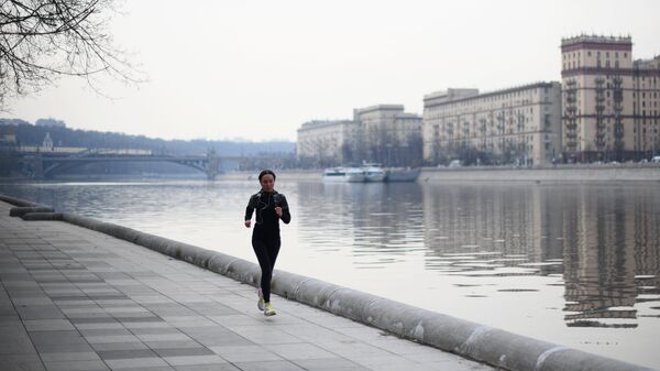 Девушка бегает по набережной возле Нескучного сада в Москве