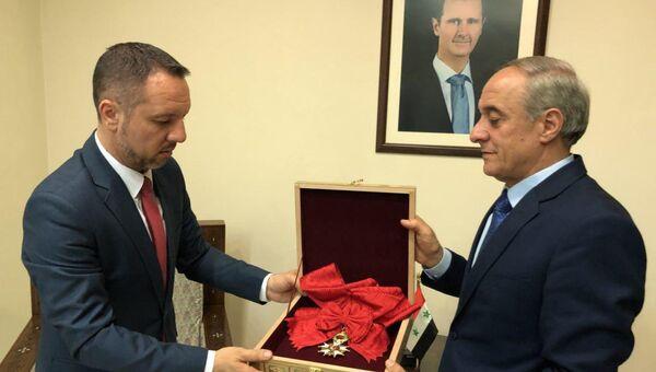 Официальный представитель САР передает Франции орден Почетного легиона Башара Асада через посольство Румынии