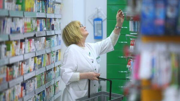 Фармацевт раскладывает лекарственные препараты