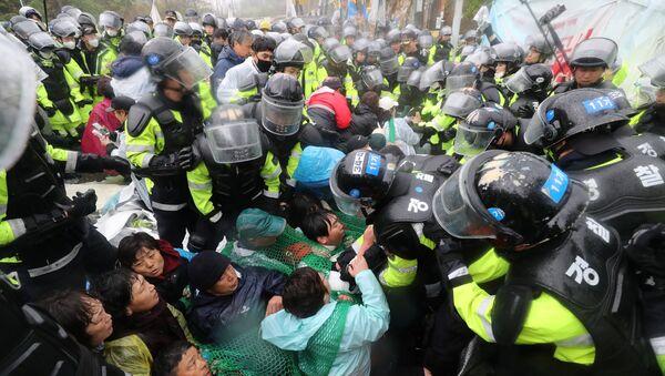 Полицейские разгоняют участников акции протеста против THAAD в Сонджу, Южная Корея. 23 апреля 2018