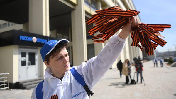 Волонтер раздаёт георгиевские ленточки. Архивное фото