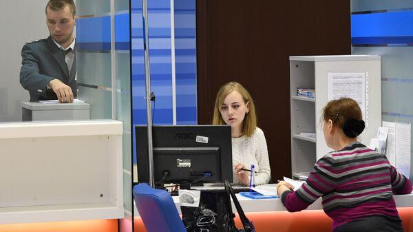 Сотрудники помогают посетительнице со сдачей налоговой отчетности в день открытых дверей в операционном зале инспекции Федеральной налоговой службы РФ в Москве